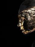 Das Gesicht der angeredeten Frau bedeckte goldene Folie über schwarzem Hintergrund. Geheimnis Lizenzfreie Stockbilder