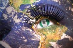 Das Gesicht der Frau mit Planet Erdbeschaffenheit und nigerische Flagge innerhalb des Auges Lizenzfreie Stockfotos