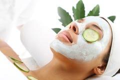 Das Gesicht der kosmetischen Verfahrensfrau in der Maskenabschwächung und in den Gurkenscheiben auf Augen Lizenzfreies Stockfoto