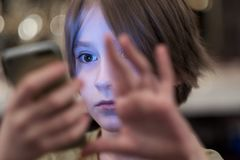 Das Gesicht des Kindes, belichtet durch den Schirm des Telefons lizenzfreie stockbilder