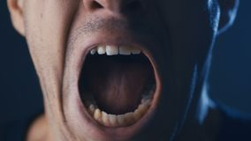 Das Gesicht des Mannes, das in der Furcht mit Handbedeckungsmund, extreme Nahaufnahme schreit stock video