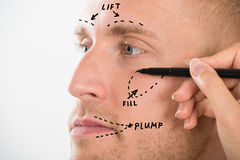 Das Gesicht des Mannes mit der Korrektur-Linie gezeichnet durch die Hand der Person Stockbild