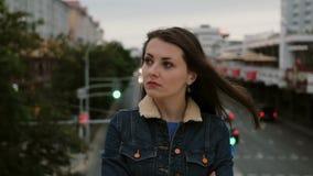 Das gestörte Mädchen, das auf Brücke steht, drückt ihre Unzufriedenheit, negativen Gefühle der Frustration und Blicke an der Kame Lizenzfreie Stockfotos