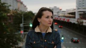 Das gestörte Mädchen, das auf Brücke steht, drückt ihre Unzufriedenheit, negativen Gefühle der Frustration und Blicke an der Kame Stockfotografie
