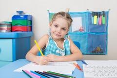 Das glückliche alte Fünfjahresmädchen zeichnet Bleistift und untersucht den Rahmen Lizenzfreie Stockfotos