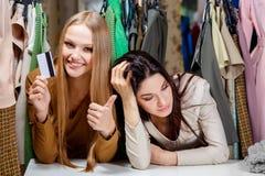 Das glückliche blonde Mädchen, welches das Einkaufen mit einer Kreditkarte, aber machen, ihr Freund hat keine Kreditkarte und tra Stockbild