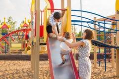 Das glückliche Freien des kleinen Jungen im Spielplatz mit seinen Eltern lizenzfreie stockfotos