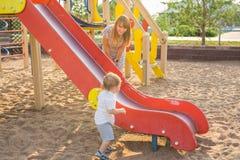Das glückliche Freien des kleinen Jungen im Spielplatz mit seinen Eltern stockbilder