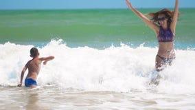 Das glückliche gebräunte Kind, das glücklich mit Mutter in den Meereswellen am sonnigen Tag des Sommers am tropischen Strand schw stock video footage