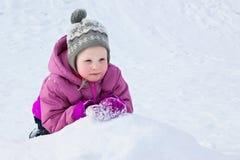 Das glückliche Kind liegt auf Schnee und beobachtet stockbild