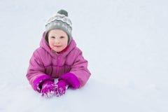 Das glückliche Kind liegt auf Schnee und lächelt Lizenzfreie Stockfotos