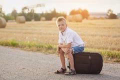 Das glückliche Kind sitzt auf einem Koffer am sonnigen Tag des Sommers, Stockbilder