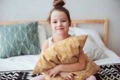 das glückliche Kindermädchen, das auf Bett und die Umarmungen pillow sitzen, am frühen Morgen, die aufwachen oder gehen zu schlaf lizenzfreie stockfotografie