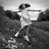 Das glückliche Kindermädchen, das auf Frühlingsmohnblume springt, blüht Lizenzfreie Stockfotografie