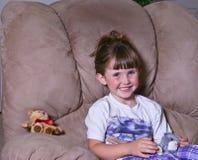 Das glückliche kleine Mädchen, das mit ihr spielt, füllte Spielwaren an lizenzfreies stockbild