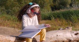 Das glückliche kleine Mädchen, das durch den Fluss, hörend Musik auf Kopfhörern sitzt und zeichnet auf die Tablette stock footage