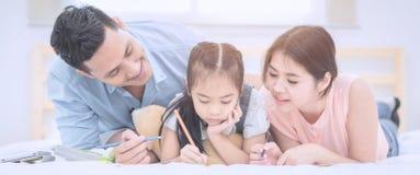 Das glückliche Lächeln der asiatischen Familie und entspannen sich auf Bett zu Hause lizenzfreie stockbilder