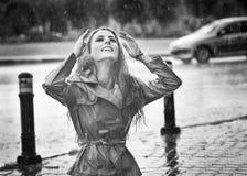 Das glückliche lange Haarmädchen, das den Regen genießt, fällt in den Park Stockfoto