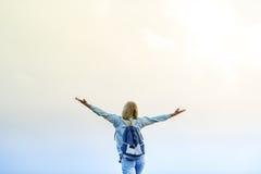 Das glückliche Mädchen mit einem Rucksack auf Sonnenuntergang Lizenzfreies Stockfoto