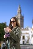 Das glückliche Mädchen in Sevilla, Spanien, mit im Hintergrund der Glockenturm der gotischen Kathedrale Lizenzfreie Stockfotografie