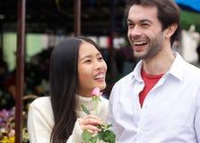 Das glückliche Paar, das mit lächelt, stieg draußen Stockfoto