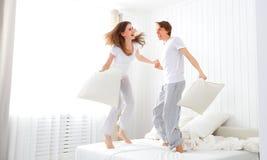 Das glückliche Paar, das Spaß im Bett springt und hat Stockbild