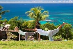 Das glückliche Paar, das Yoga macht, trainiert draußen Lizenzfreies Stockfoto