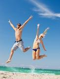 das glückliche Paar springend auf den Strand Lizenzfreie Stockfotografie