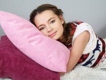 Das glückliche schöne Mädchen liegt auf rosafarbenen Kissen stockfotos