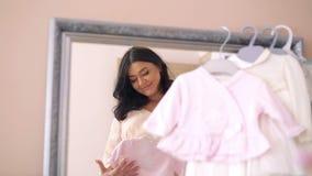 Das glückliche schwangere Schauen über Baby kleidet auf einem Spiegelhintergrund 4K stock video