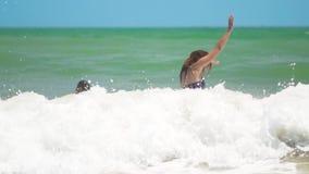Das gl?ckliche gebr?unte Kind, das gl?cklich mit Mutter in den Meereswellen am sonnigen Tag des Sommers am tropischen Strand schw