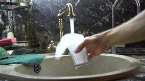 Das Glas wird mit Wasser in einer Wanne gewaschen stock video footage