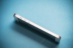 Das Gold-Apple-iPhone 5s auf Hintergrund des blauen Papiers Stockfotografie