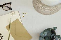 Das goldene geöffnete Notizbuch, der Bleistift, die Büroklammern, die Stifte, der Umschlag, die Schauspiele und der Hut auf dem T stockfotografie