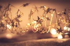 Das goldene Glänzen spielt Girlande mit funkelnden Weihnachtslichtern in den goldenen Farben in der Heiligen Nacht als Luxusweihn Stockfotografie