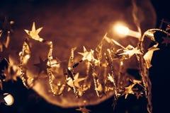 Das goldene Glänzen spielt mit funkelnden Weihnachtslichtern in den goldenen Farben in der Heiligen Nacht als Weihnachtshintergru Stockfotos