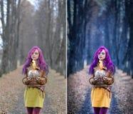 Das gotische Mädchen mit dem purpurroten Haar steht mit einem Brennglas in ihren Händen in der Gasse im Herbstwaldkonzept redigie Stockbild