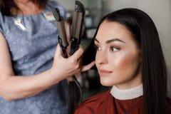 Das Grinsen der Frau erhält Haar getan mit zhuzh im Salon stockfoto