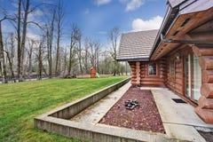 Das große Blockhaushaus, das mit Gras außen ist, füllte Hinterhof Stockfotos