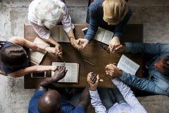 Das Gruppe von Personenen-Händchenhalten, das Anbetung betet, glaubt