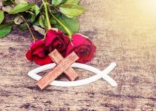 Das hölzerne Kreuz mit roten Rosen auf Holztisch Lizenzfreies Stockfoto