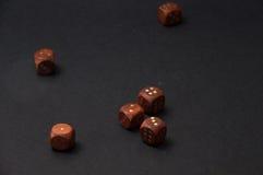 Das hölzerne Spielen würfelt auf schwarzem Hintergrund Stockfoto