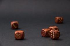 Das hölzerne Spielen würfelt auf schwarzem Hintergrund Lizenzfreie Stockfotos