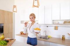 Das hübsche aufwerfende Mädchen und isst Kartoffelchips, steht in der Mitte von ki Lizenzfreie Stockfotografie