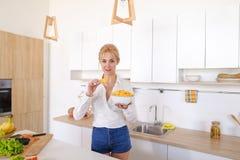 Das hübsche aufwerfende Mädchen und isst Kartoffelchips, steht in der Mitte von ki Lizenzfreie Stockbilder