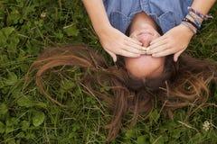 Das hübsche Mädchen, das auf dem Gras liegt, schließt seine Augen mit seinen Händen Probleme der Jugendlicher Lizenzfreie Stockfotos