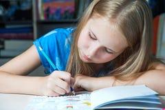 Das hübsche Mädchen, das bei Tisch mit erwachsenem Malbuch sitzt, zeichnet an Lizenzfreie Stockfotografie