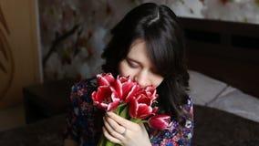 Das hübsche Mädchen, das eine Blume schnüffelt, betrachtet playfully die Kamera und das Lächeln stock footage