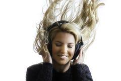 Das hübsche Mädchen, das Haar-hörende Kopfhörer schleudert, lokalisierte Hintergrund Lizenzfreies Stockfoto
