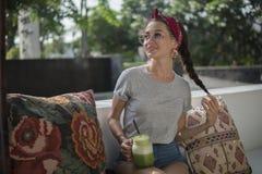 Das hübsche Modell, das auf Bank mit Kissen im Café im Freien, dunkelhaarige Schönheit aufwirft, hält ihren Haarzopf in einer Han lizenzfreies stockfoto